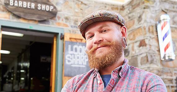 IDEAL PflegeTagegeld: Freundlicher Friseur vor seinem Friseursalon