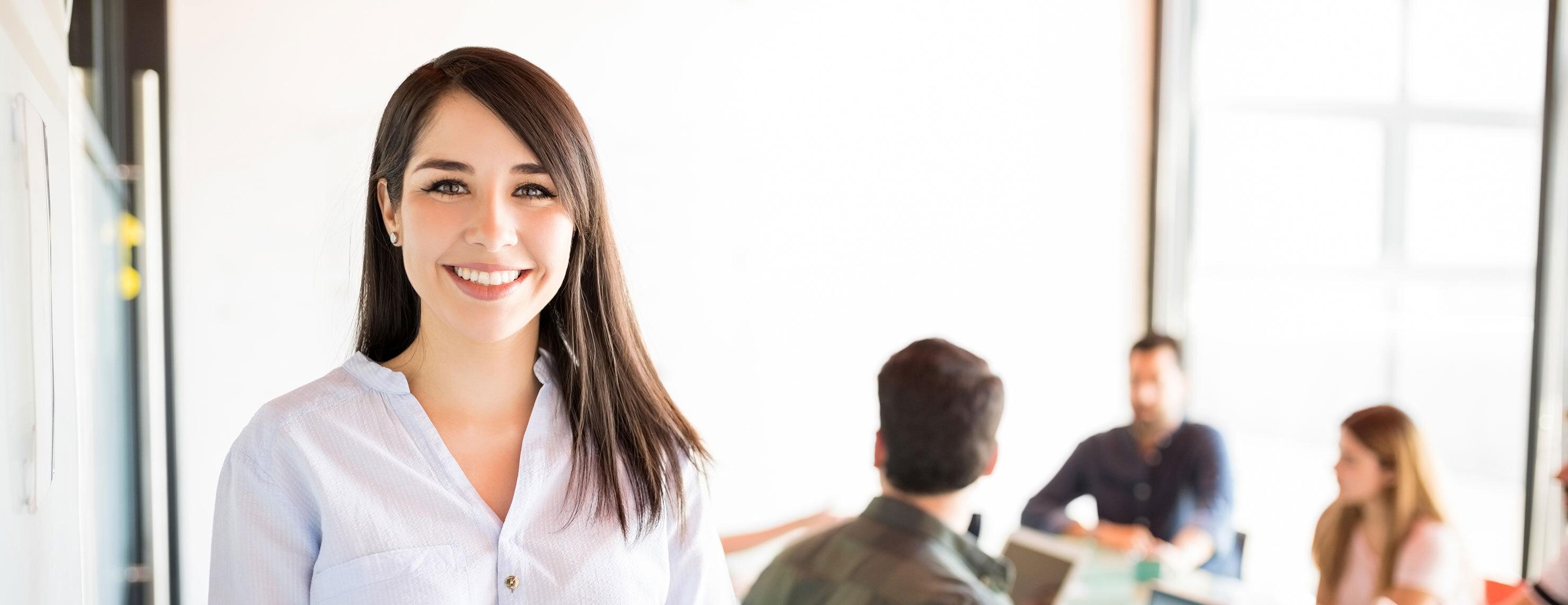 Junge Frau im Meetingraum mit KollegInnen im Hintergrund