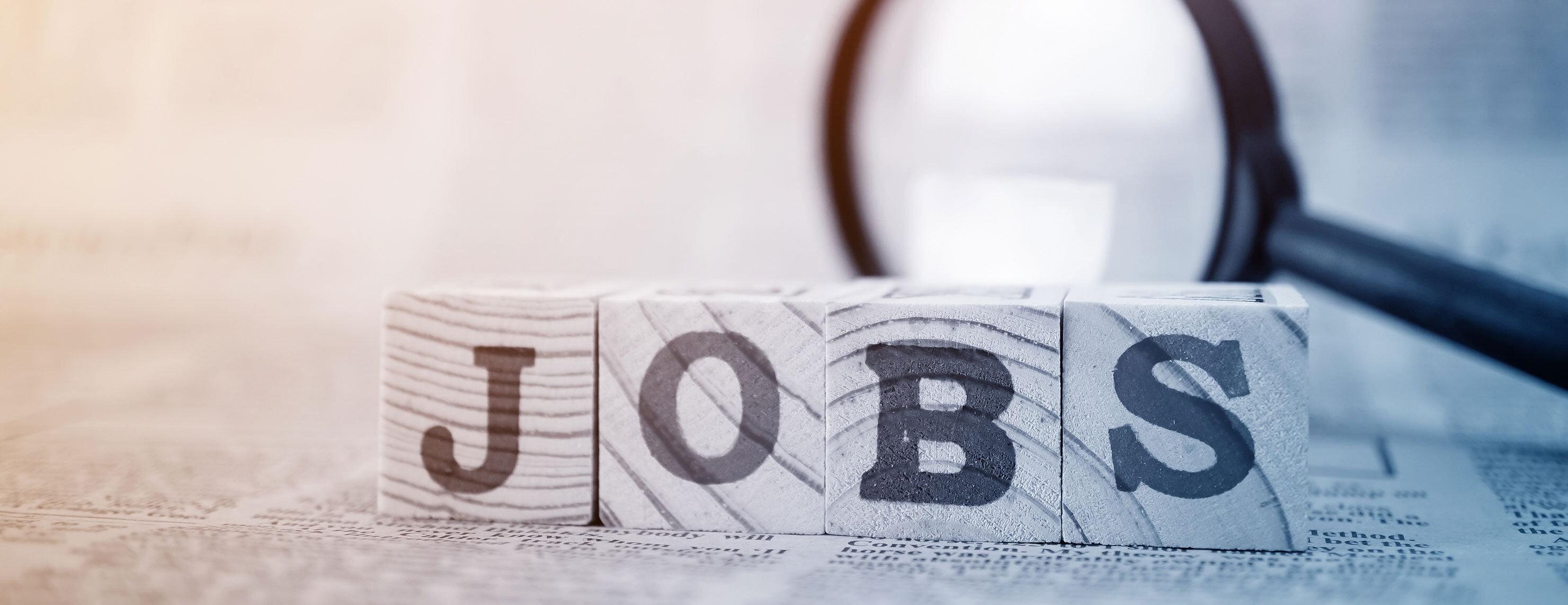 Vier Holzwürfel mit der Aufschrift Jobs
