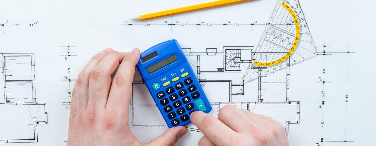 Mann berechnet Wohnraum mit Taschenrechner und Wohnungsplan