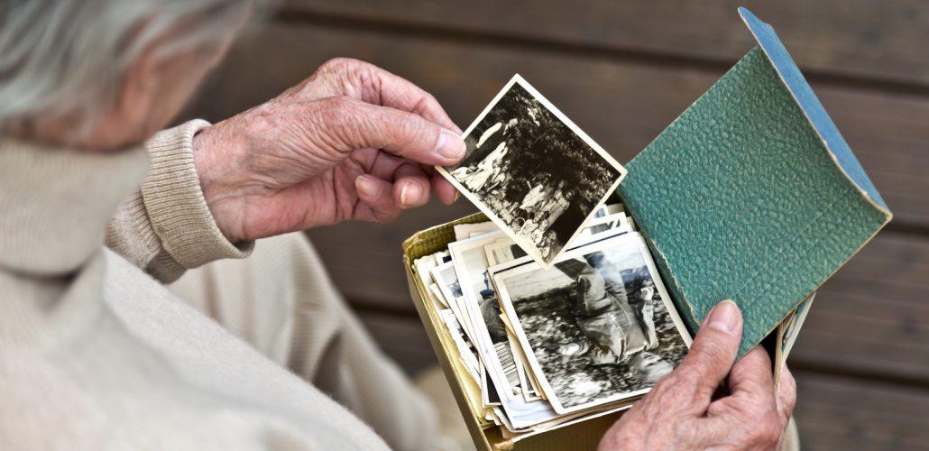 Demenz - demente Frau, die sich Fotos anschaut