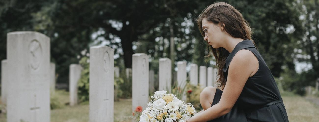 Frau mit Blumenstraß kniet vor Grab