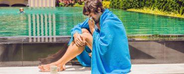 Mann sitzt am Schwimmbad und schneuzt sich die Nase