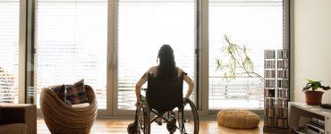 Eine junge Frau sitzt in einem Rollstuhl vor einem großen Fenster. Sie ist bereits in jungen Jahren ein Pflegefall.