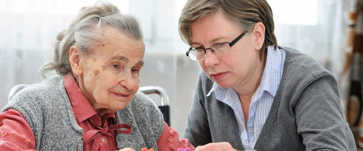Eine alte Dame puzzelt mit einer Pflegerin des Pflegeheims am Tisch