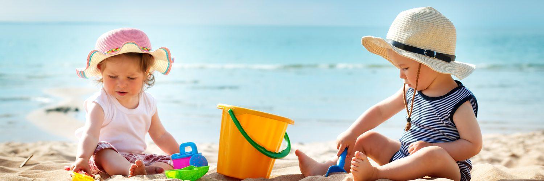 Zwei Kleinkinder spielen am Strand in der Sonne mit ausreichend Sonnenschutz