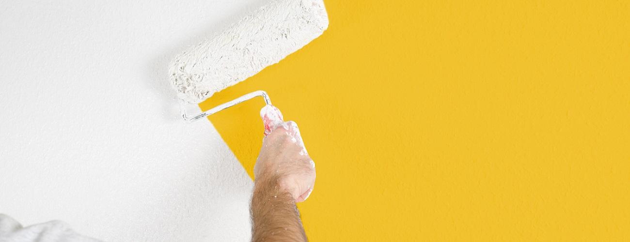 Maler streicht gelbe Wand weiß