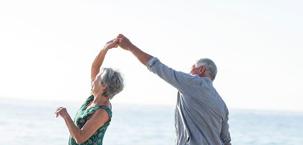Den Ruhestand genießen: Älteres Paar tanzt am Strand
