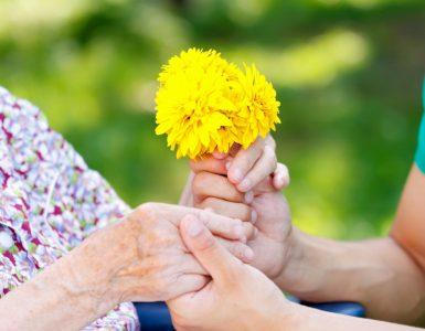 Demenz - Hände, die Blumen umschließen