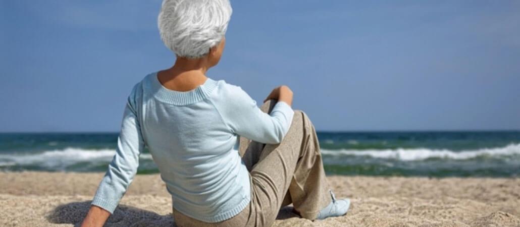 Frau am Strand sitzend und aufs Meer blickend