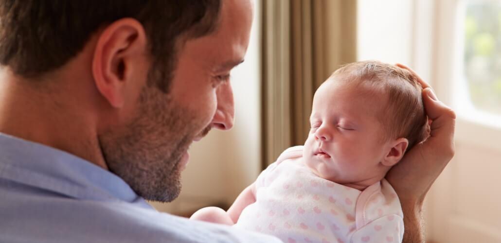 Junger Vater mit Säugling im Arm