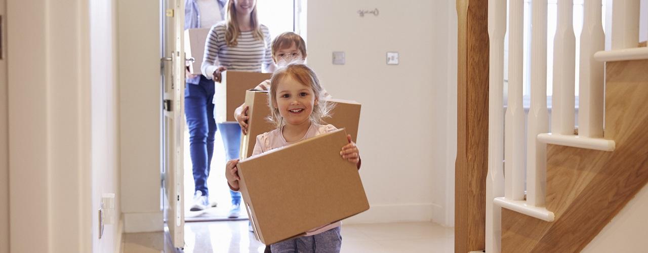 Familie trägt Umzugskartons, Hausrat ins neue Haus