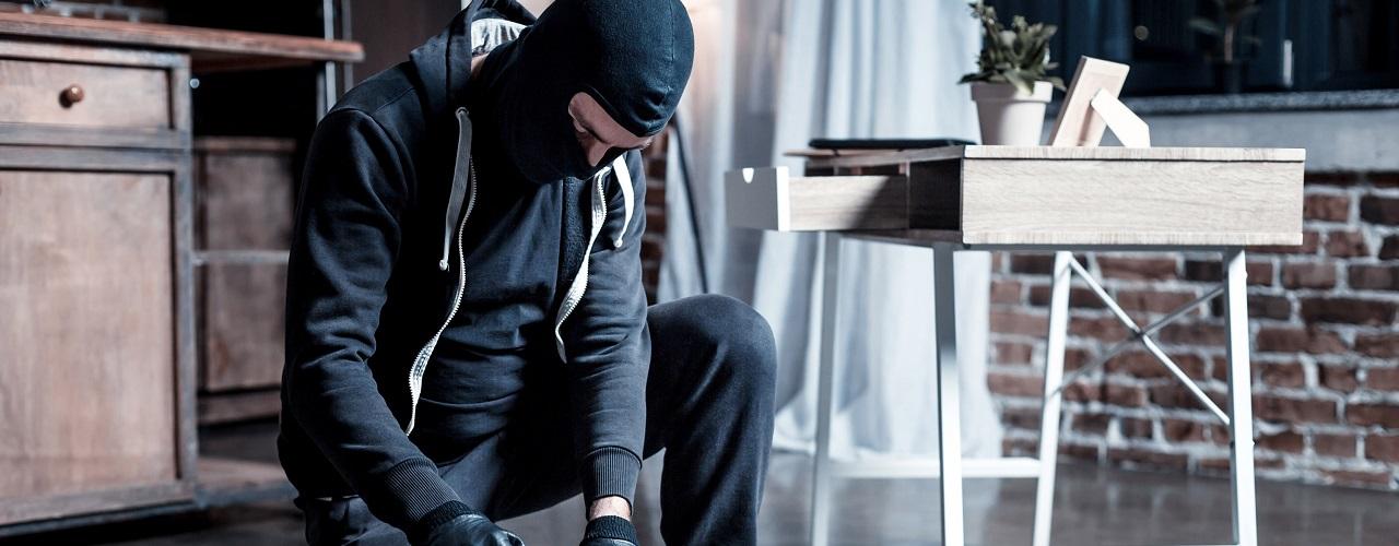 Maskierter Einbrecher durchsucht den Hausrat