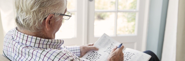 Älterer Mann sitzt im Sessel und löst ein Kreuzworträtsel