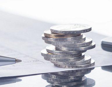 Taschenrechner mit Stift und Euro-Münzen
