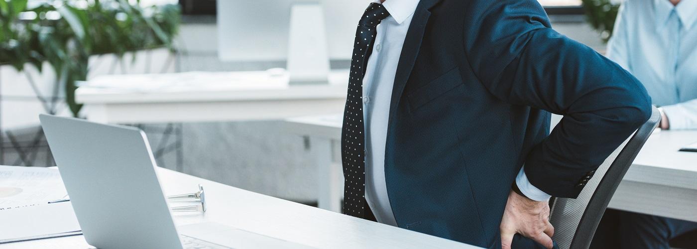 Mann mit Rückenschmerzen am Arbeitsplatz