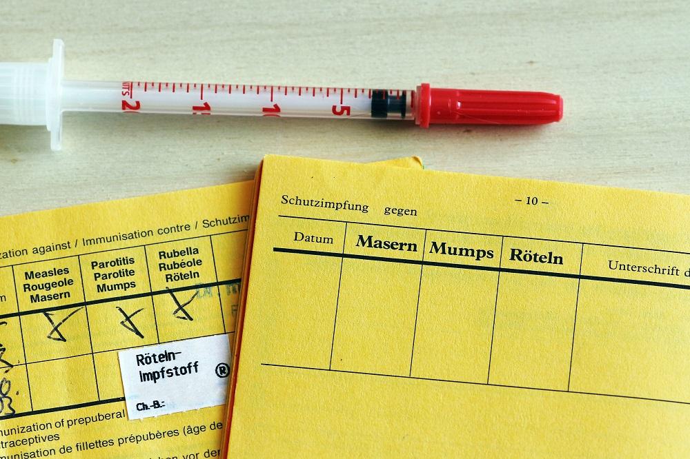Bild eines Impfausweises und einer Spritze