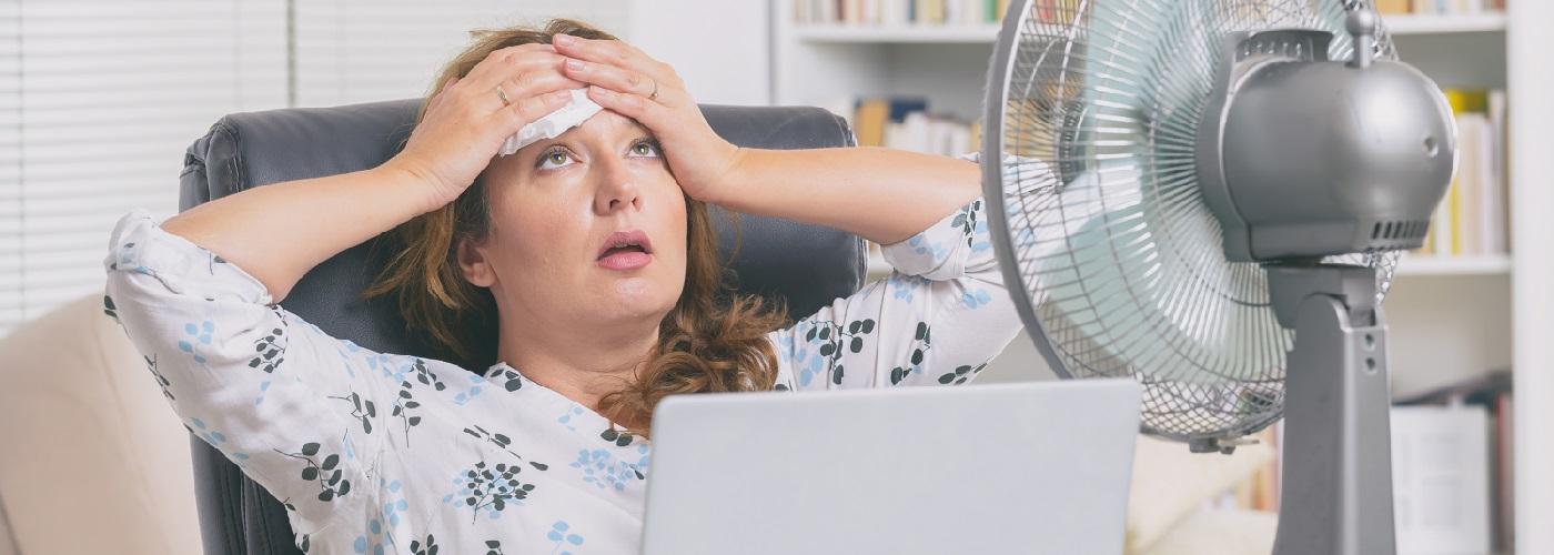 Frau schwitzt vor Hitze im Büro und kühlt sich mit einem Ventilator ab