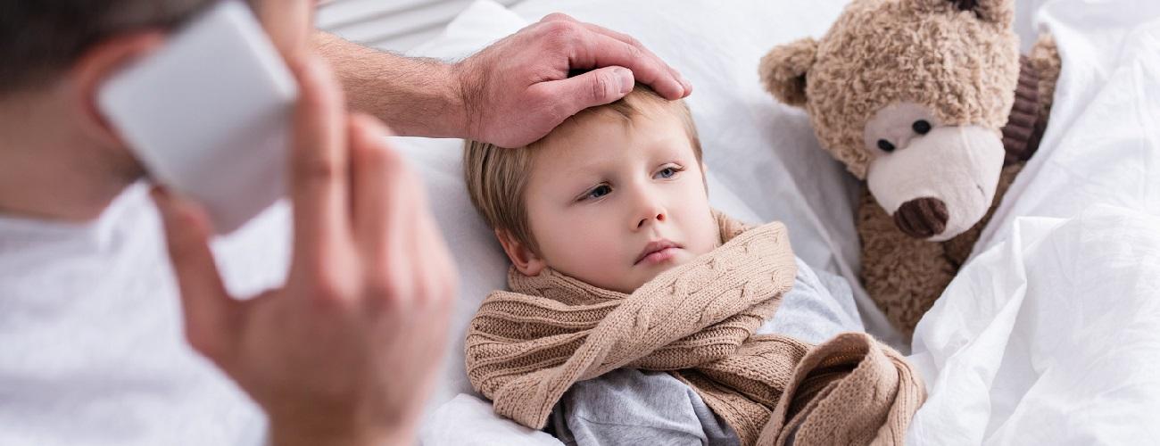Vater kümmert sich um seinen kranken Sohn im Bett