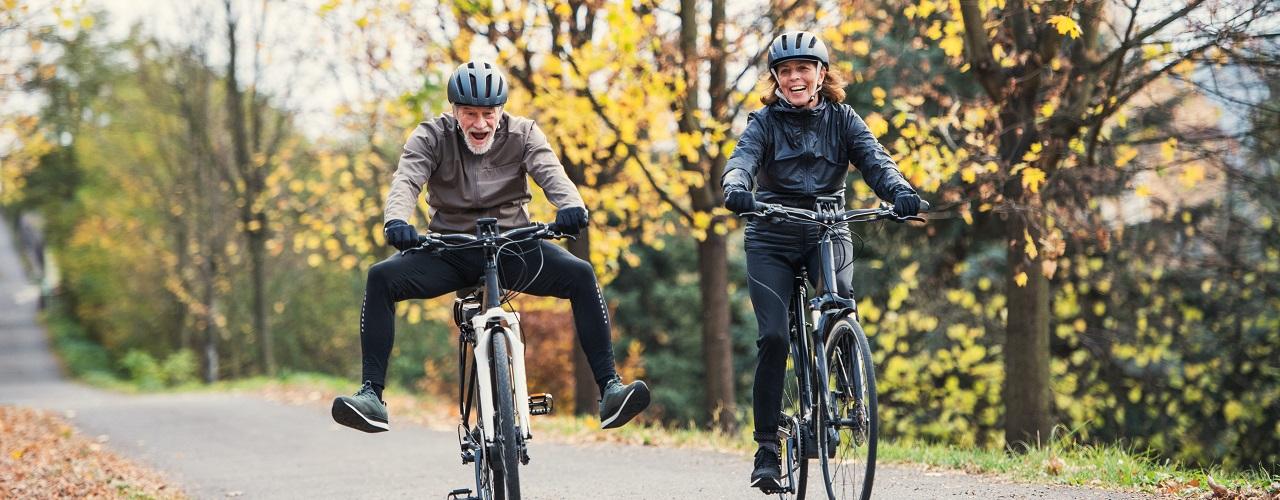 Zwei Personen fahren mit einem E-Bike oder Pedelec einen Waldweg entlang