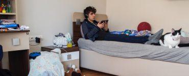 Junge sitzt in einem unordentlichen Zimmer