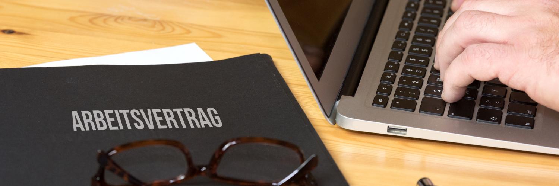 Arbeitsvertrag auf Tisch mit Brille darauf