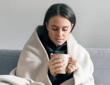 Frau mit Tee und Decke auf Sofa