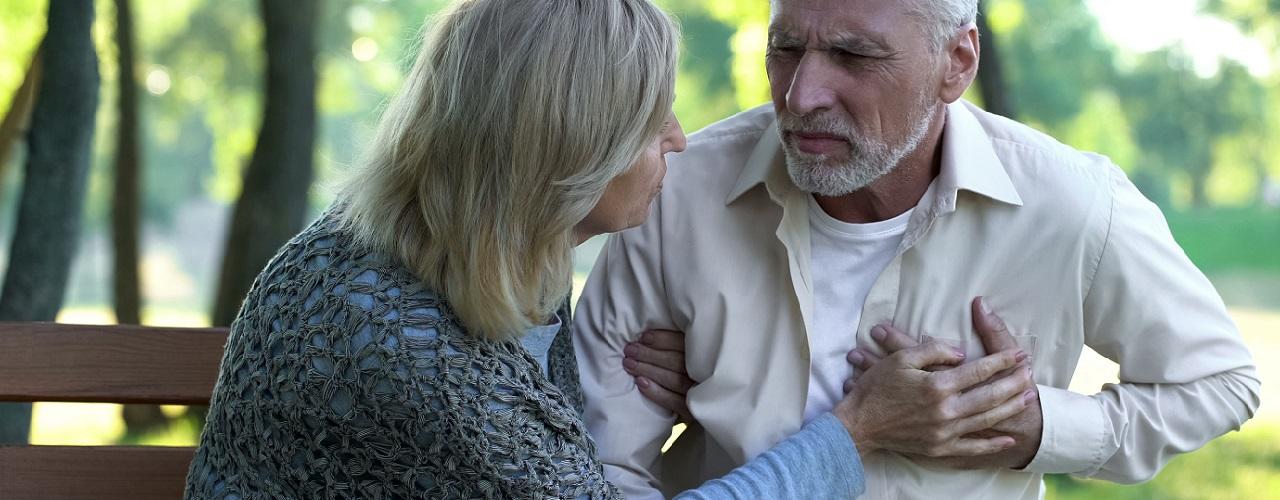 Mann und Frau sitzen auf einer Parkbank während der Mann Brustschmerzen andeutet