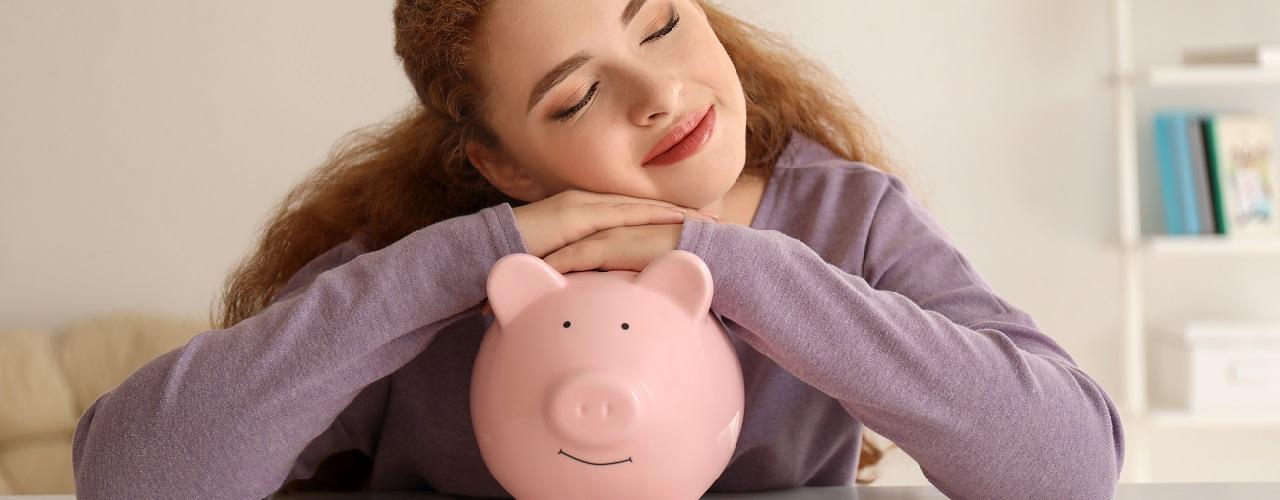 Junge Frau träumt auf Sparschwein