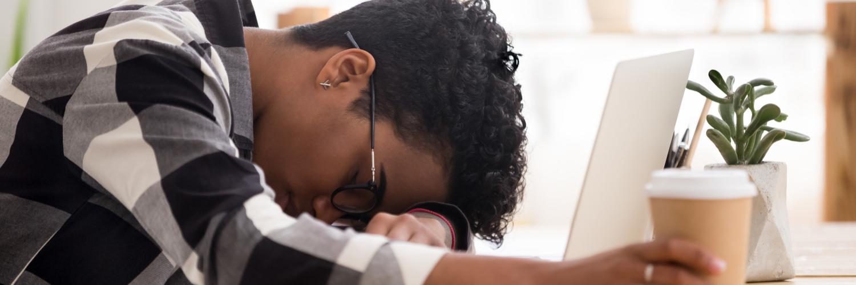 Frau liegt mit Kopf auf Schreibtisch