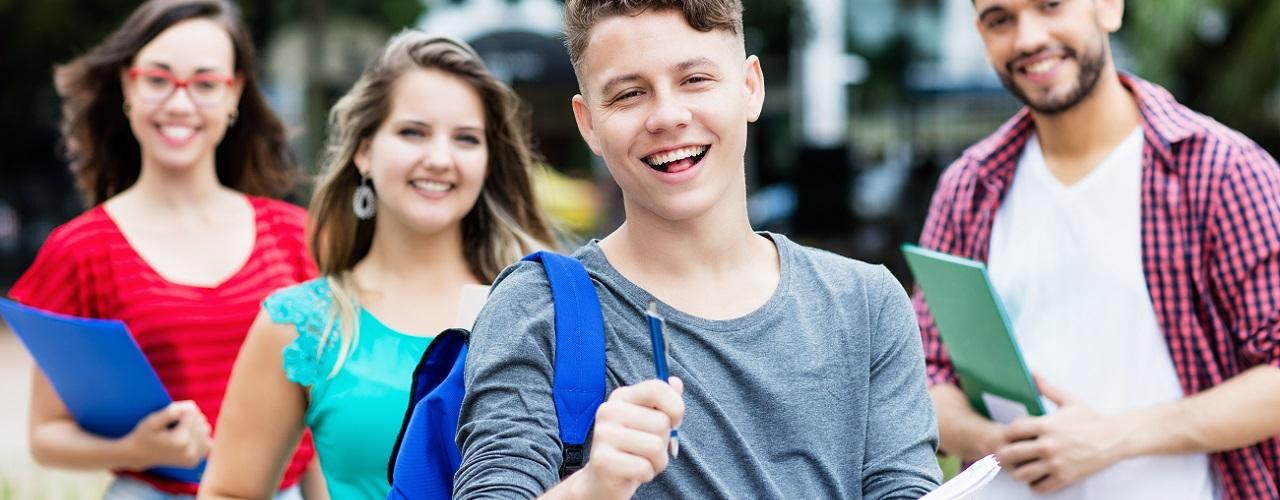 Vier Jugendliche blicken mit Bewerbungen in die Kamera und sind bereit für ihre Ausbildungssuche