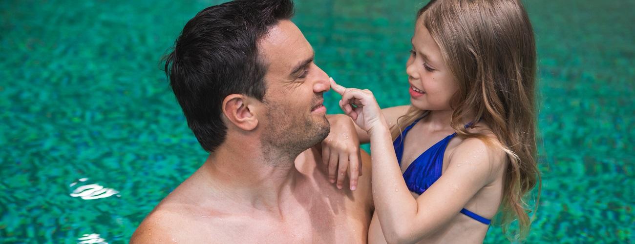 Vater spielt mit seiner Tochter im Schwimmbad