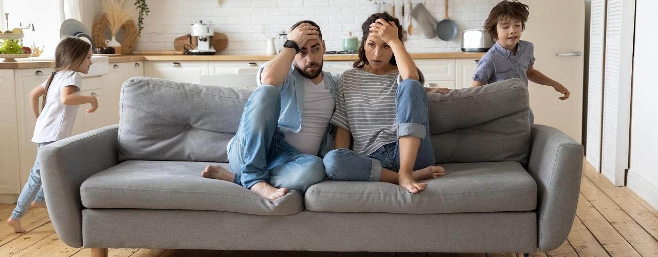 Müde Eltern sitzen auf der Couch und Kinder rennen durch die Wohnung