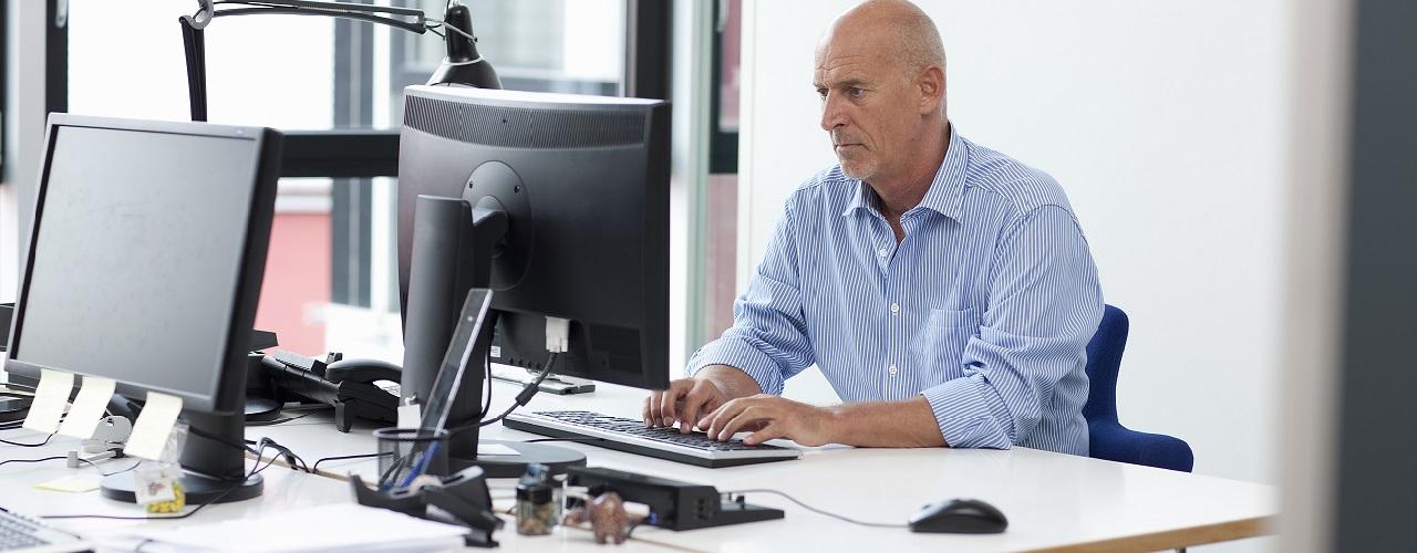 Mann sitzt im Buero am Computer