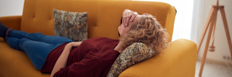 Frau liegt erschöpft im Bett