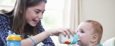 Mädchen füttert Baby mit Trinkflasche