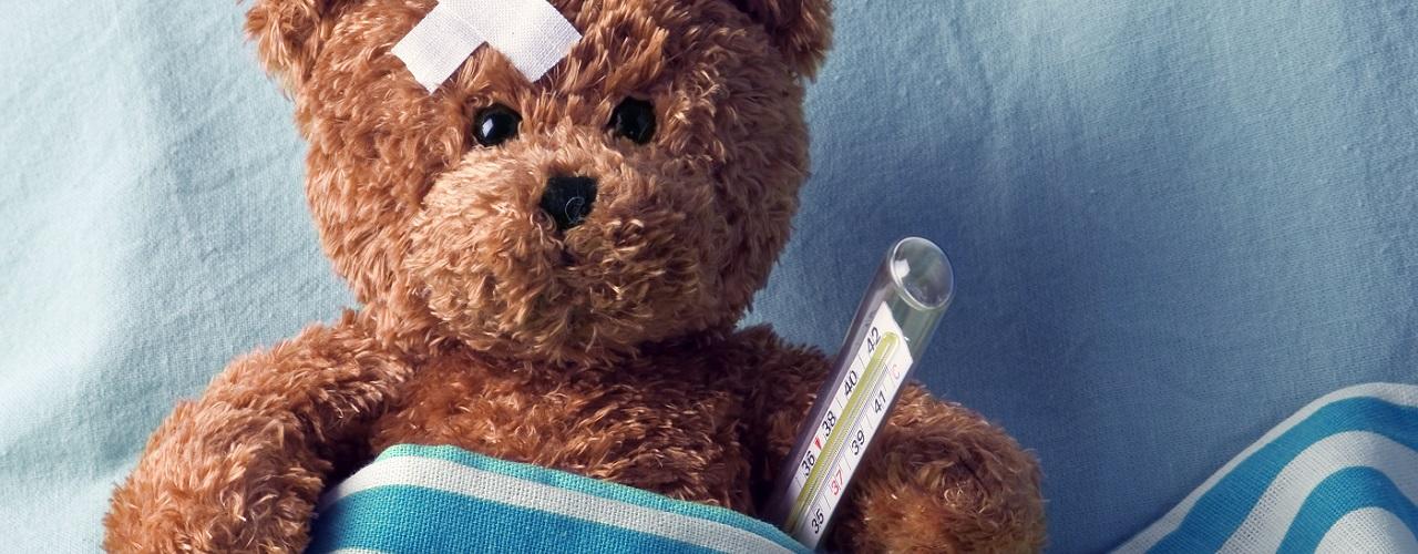 Teddybär mit Pflaster auf dem Kopf und Thermometer im Krankenbett