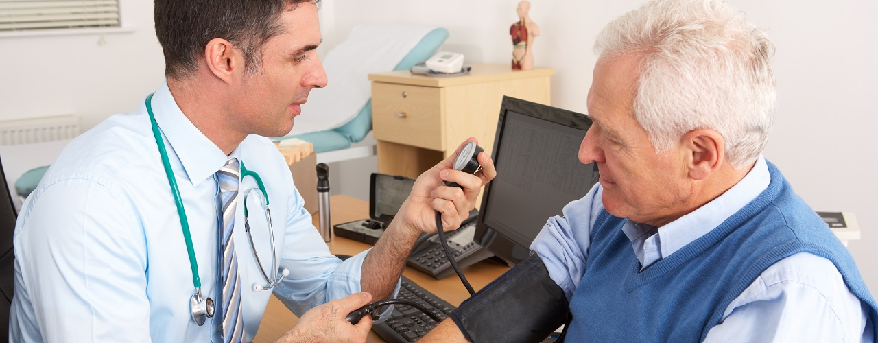 Arzt misst Blutdruck von Mann