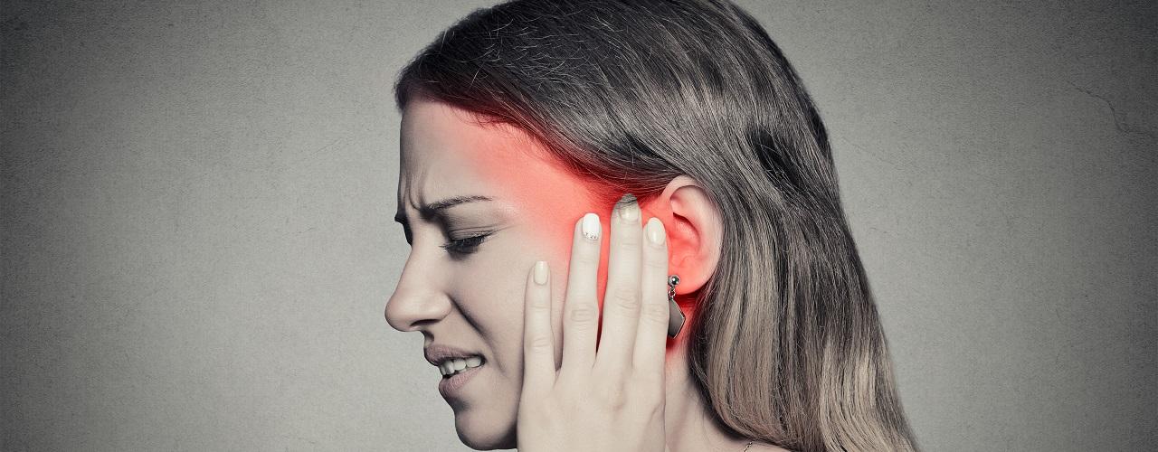 Frau mit Ohrenschmerzen und Tinnitus