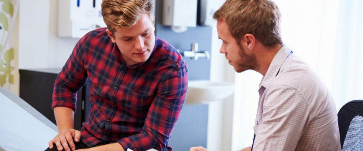 Junger Mann im Gespräch zur Krebsvorsorge mit seinem Arzt