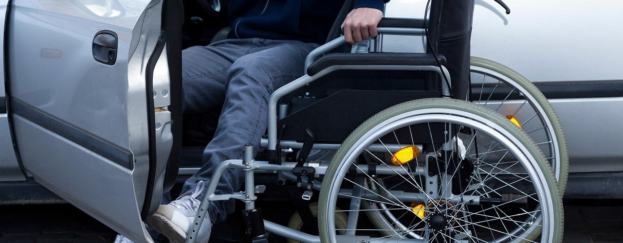 Mann im Rollstuhl steigt in sein Auto ein