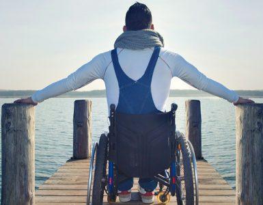 Mann in Rollstuhl auf Steg am See