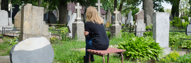 Frau sitzt auf Bank auf Friedhof