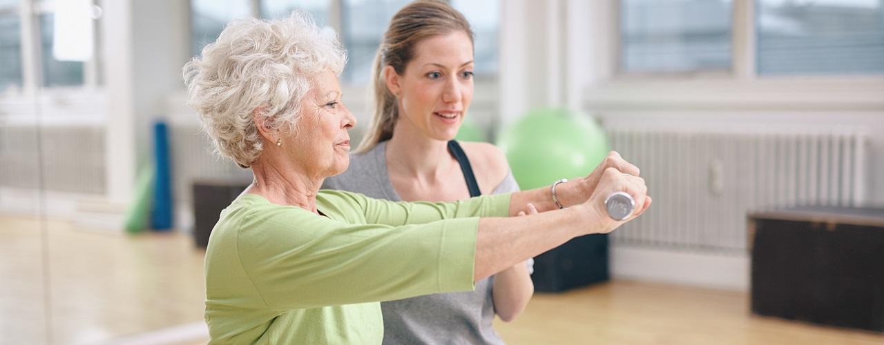 Seniorin übt mit einem Trainingsball und Therapeutin.