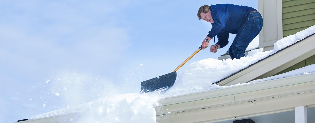 Mann schaufelt Schnee vom Dach