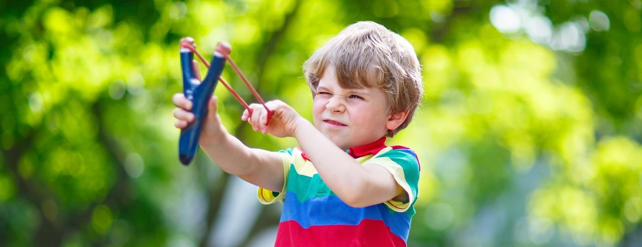 Kleiner Junge schießt mit Steinschleuder im Wald