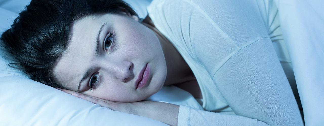 Eine junge Frau liegt Nachts wach im Bett