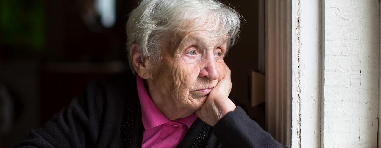 Melancholische alte Frau blickt aus dem Fenster auf der Suche nach einem Weg aus der Einsamkeit