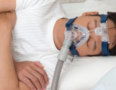 Mann liegt mit Beatmungsgerät im Bett und schläft