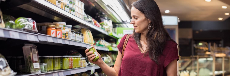 Frau prüft im Supermarkt Lebensmittel